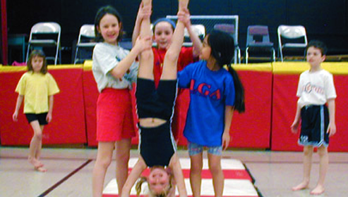 Students helping another student doing a handstand